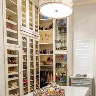 Ispirazione per una grande cabina armadio per donna classica con ante in legno chiaro, pavimento in legno massello medio e ante di vetro