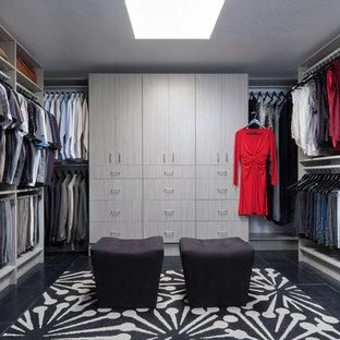 Immagine di una grande cabina armadio unisex moderna con ante lisce, ante in legno chiaro, pavimento in gres porcellanato e pavimento nero