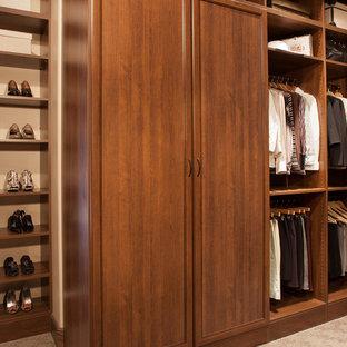 Modelo de armario vestidor unisex, tradicional renovado, de tamaño medio, con puertas de armario de madera en tonos medios, moqueta y armarios con paneles empotrados