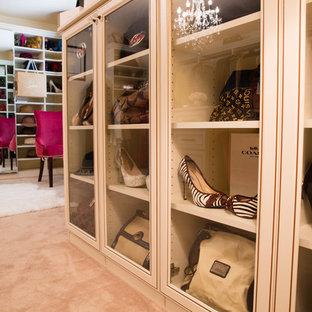Imagen de armario vestidor de mujer, minimalista, grande, con armarios con paneles con relieve, puertas de armario blancas y moqueta
