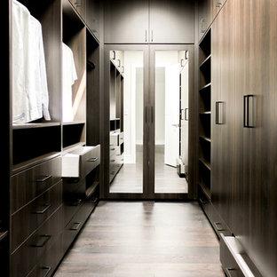 Imagen de armario vestidor unisex, actual, de tamaño medio, con armarios con paneles lisos, puertas de armario de madera en tonos medios, suelo de madera clara y suelo marrón