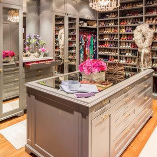 Diseño de armario vestidor de mujer, tradicional renovado, grande, con armarios estilo shaker, puertas de armario grises y suelo de madera clara
