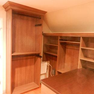 Diseño de armario vestidor unisex, tradicional, grande, con armarios con paneles lisos y suelo de madera clara