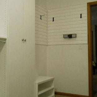 Esempio di un'ampia cabina armadio unisex minimalista con ante lisce, ante bianche e moquette
