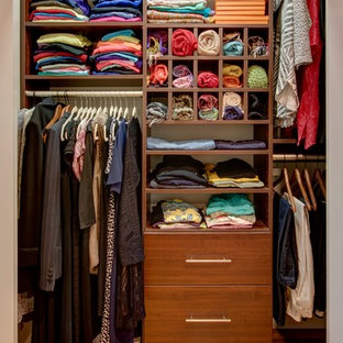 Reach-in closet - small transitional gender-neutral medium tone wood floor and beige floor reach-in closet idea in New York with flat-panel cabinets and dark wood cabinets