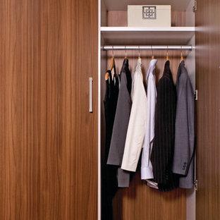 Diseño de armario unisex, tradicional, de tamaño medio, con suelo de madera en tonos medios, armarios con paneles lisos y puertas de armario de madera oscura