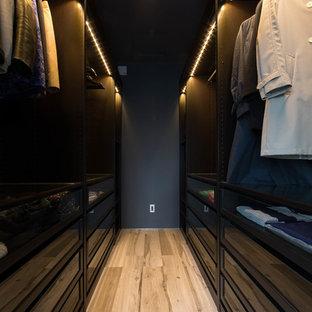 Foto de armario y vestidor de hombre, actual, con puertas de armario negras, suelo de madera clara y suelo beige