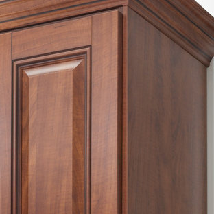 Diseño de armario vestidor clásico con armarios con paneles con relieve, puertas de armario de madera en tonos medios y suelo de madera oscura