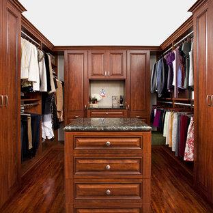 Foto di una cabina armadio classica con ante con bugna sagomata e ante in legno bruno