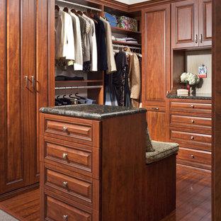 Imagen de armario vestidor clásico con armarios con paneles con relieve, puertas de armario de madera en tonos medios y suelo de madera oscura