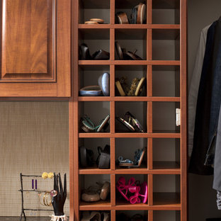 Traditional walk-in wardrobe in Philadelphia with raised-panel cabinets, dark wood cabinets and dark hardwood floors.