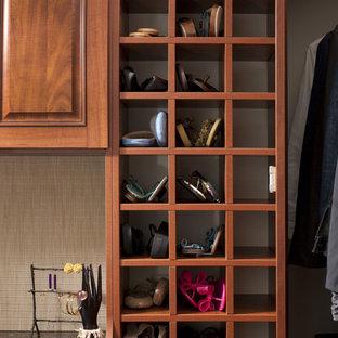 Cette photo montre un dressing chic avec un placard avec porte à panneau surélevé, des portes de placard en bois sombre et un sol en bois foncé.
