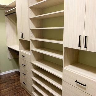 Diseño de armario y vestidor costero con armarios con paneles lisos, puertas de armario de madera clara, suelo de madera oscura y suelo marrón