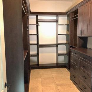 Diseño de armario vestidor unisex, clásico renovado, grande, con armarios con rebordes decorativos, puertas de armario negras, suelo de baldosas de porcelana y suelo beige