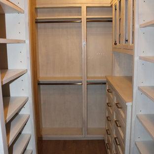 Idee per uno spazio per vestirsi unisex minimalista di medie dimensioni con nessun'anta, ante con finitura invecchiata e pavimento in legno massello medio