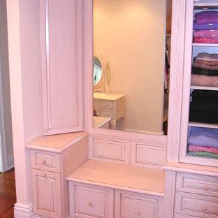 Ejemplo de vestidor unisex, clásico, de tamaño medio, con armarios abiertos, puertas de armario con efecto envejecido y suelo de madera en tonos medios