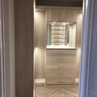 Diseño de armario vestidor unisex, actual, de tamaño medio, con armarios con paneles lisos, puertas de armario de madera oscura, suelo de madera en tonos medios y suelo multicolor