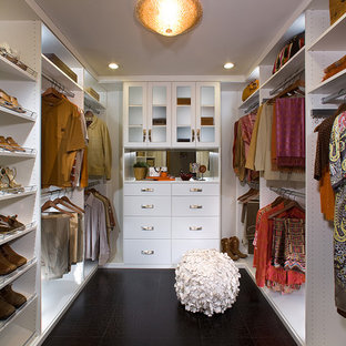 Idée de décoration pour un dressing design neutre avec un placard à porte plane, des portes de placard blanches et un sol noir.