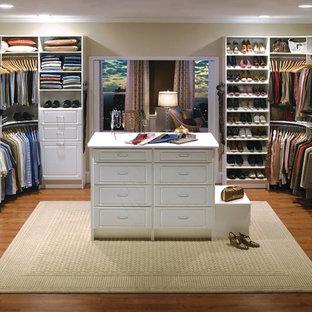 Esempio di un grande spazio per vestirsi unisex classico con ante con bugna sagomata, ante bianche, pavimento in legno massello medio e pavimento marrone