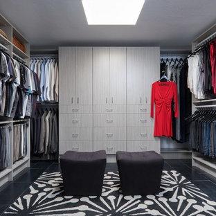 Réalisation d'un grand dressing room minimaliste neutre avec un placard à porte plane, des portes de placard en bois clair, un sol en carrelage de porcelaine et un sol noir.