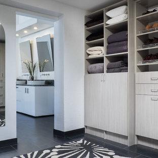 Foto de vestidor unisex, moderno, grande, con armarios con paneles lisos, puertas de armario de madera clara, suelo de baldosas de porcelana y suelo negro