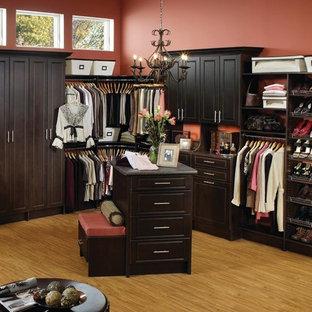 Ejemplo de vestidor unisex, tradicional, grande, con armarios con paneles con relieve, puertas de armario negras, suelo de madera clara y suelo marrón