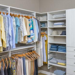 Inspiration pour un grand dressing style shabby chic neutre avec des portes de placard blanches.