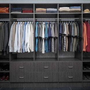 Cette photo montre un dressing tendance de taille moyenne pour un homme avec un placard à porte plane, des portes de placard grises et un sol en carrelage de porcelaine.