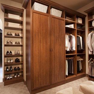 Idee per una grande cabina armadio unisex chic con ante con bugna sagomata, ante in legno bruno e moquette
