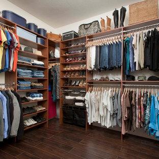 Ejemplo de armario vestidor unisex, clásico renovado, de tamaño medio, con armarios con paneles lisos, puertas de armario de madera oscura y suelo de baldosas de porcelana