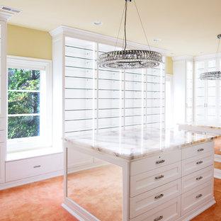 Ejemplo de armario vestidor de mujer, tradicional renovado, extra grande, con armarios tipo vitrina, puertas de armario blancas y moqueta