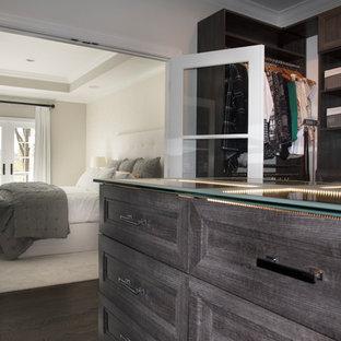 Esempio di una cabina armadio unisex tradizionale di medie dimensioni con ante con riquadro incassato, ante con finitura invecchiata, parquet scuro e pavimento marrone