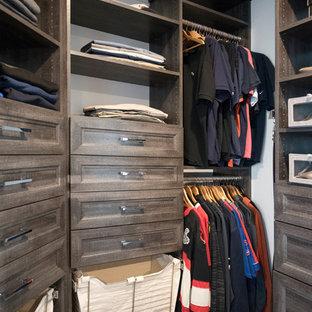 Diseño de armario vestidor unisex, clásico renovado, de tamaño medio, con armarios con paneles empotrados, puertas de armario con efecto envejecido, suelo de madera oscura y suelo marrón