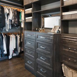 Diseño de armario vestidor unisex, tradicional renovado, de tamaño medio, con armarios con paneles empotrados, puertas de armario con efecto envejecido, suelo de madera oscura y suelo marrón