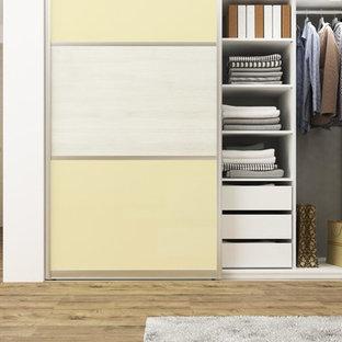 Imagen de armario minimalista, de tamaño medio, con armarios con paneles lisos y puertas de armario amarillas