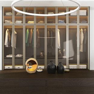 Bild på ett mellanstort funkis klädskåp, med luckor med glaspanel