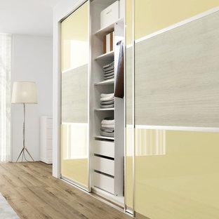 ニューヨークの中くらいのモダンスタイルのおしゃれな壁面クローゼット (フラットパネル扉のキャビネット、黄色いキャビネット) の写真