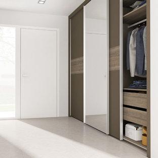 Ejemplo de armario minimalista, de tamaño medio, con armarios con paneles lisos y puertas de armario marrones