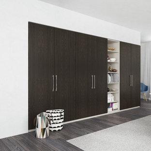 Imagen de armario moderno, de tamaño medio, con armarios con paneles lisos y puertas de armario de madera en tonos medios