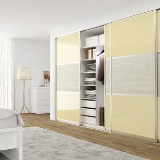 На фото: шкаф в нише среднего размера в стиле модернизм с плоскими фасадами и желтыми фасадами с
