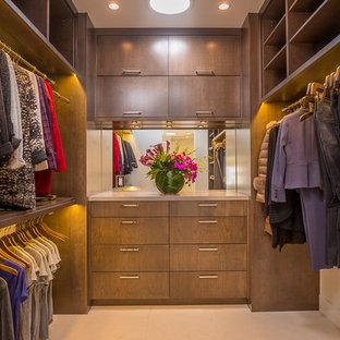 ロサンゼルスの広い男女兼用コンテンポラリースタイルのおしゃれなウォークインクローゼット (フラットパネル扉のキャビネット、中間色木目調キャビネット、ライムストーンの床) の写真