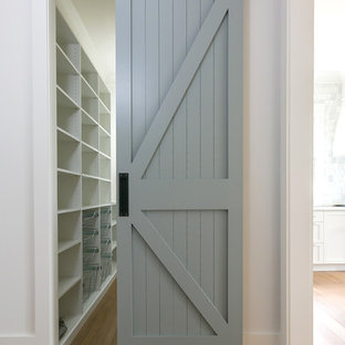 Walk-in closet - small coastal gender-neutral medium tone wood floor and brown floor walk-in closet idea in Charleston with open cabinets and white cabinets