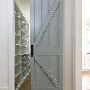 Diseño de armario vestidor unisex, costero, pequeño, con armarios abiertos, puertas de armario blancas, suelo de madera en tonos medios y suelo marrón