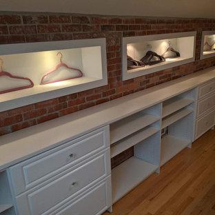 Ejemplo de armario vestidor unisex, ecléctico, grande, con armarios con rebordes decorativos, puertas de armario blancas y suelo de madera en tonos medios