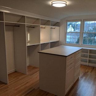 Ejemplo de armario vestidor unisex, bohemio, grande, con armarios con rebordes decorativos, puertas de armario blancas y suelo de madera en tonos medios