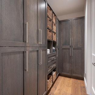 Foto di una cabina armadio unisex minimalista di medie dimensioni con ante in stile shaker, ante marroni, pavimento in legno massello medio e pavimento marrone