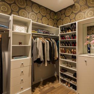 Ejemplo de armario vestidor de mujer, tradicional renovado, de tamaño medio, con puertas de armario blancas, suelo de madera en tonos medios y armarios con paneles lisos