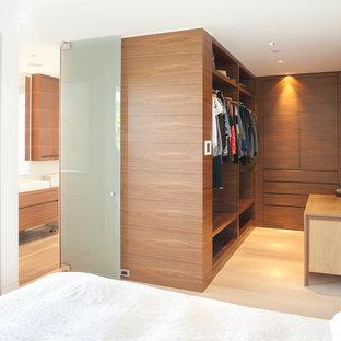 Ejemplo de armario vestidor contemporáneo con suelo de bambú, armarios con paneles lisos, puertas de armario de madera en tonos medios y suelo beige