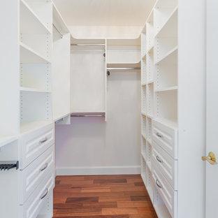 Cette photo montre un dressing craftsman de taille moyenne et neutre avec un placard avec porte à panneau surélevé, des portes de placard blanches, un sol en bois brun et un sol marron.
