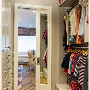 Cette image montre un petit dressing design pour une femme avec des portes de placard grises et un sol en bois brun.